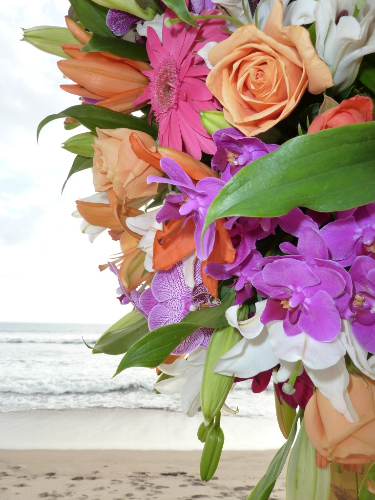 Flower arrangement on the beach at wedding vow renewal by wedding planner Randy Gritz