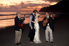 Singers playing the guitar around a wedding couple on the beach